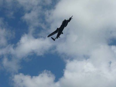 Čtyřmotorový Lancaster prolétá nad Pegasus Bridge.